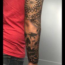 Realistic skull forearm tattoo by Simon Halpern at 1 Point Tattoo
